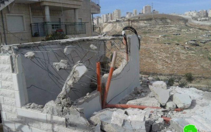 مواطن يقوم مجبراً على هدم مسكنه ذاتياً تنفيذاً لقرار بلدية الاحتلال في قرية العيسوية
